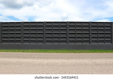 Black concrete surrounding wall with stripe of grass and an asphalt road in front. Cloudy sky above. Background for copy space