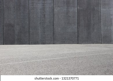 Black concrete wall with an asphalt road in front. Background for copy space