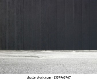 Black concrete wall with vertical stripes and an asphalt road in front. Background for copy space