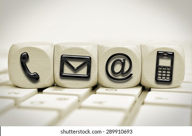 black contact us symbols on cubes on a keyboard
