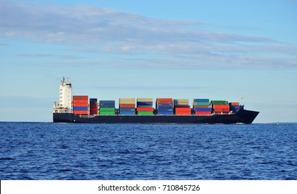 Black container ship sailing in calm water near port of Riga