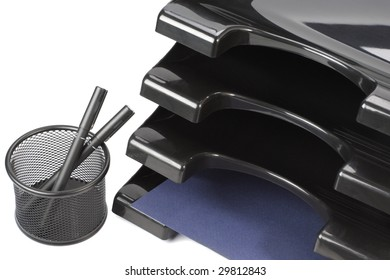 Black containers with paper and container with pens isolated on white background.