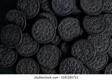 A lot of black cookies with a white cream center on a black canvas background in dark colors.