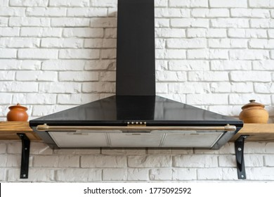 Black cooking hood with buttons and light against copy space on white brick wall. Kitchen appliance in apartment with modern interior