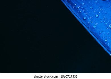 Black copy space for text. Water drops on waterproof nylon fabric. Macro detail view of texture of blue textile synthetic waterproof clothing. morning dew on camping tent close view. Rain