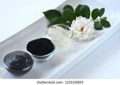 Black cosmetic activated charcoal powder, fresh aloe vera gel and beauty face mask  mixture on white. Oily skin, detox and acne treatment.