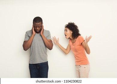 Black couple arguing. Angry african-american woman shouting at boyfriend at white studio background, copy space. Break up or divorce, family misunderstanding concept, isolated