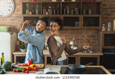 Black couple dancing near table with food in kitchen. Family having fun while cooking