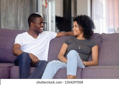 Black couple or just friends sitting on sofa in living room communicating talking at home spouses looking at each other smiling laughing chatting planning enjoy time together love flirt dating concept