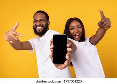 Black couple showing blank empty smartphone screen for mockup - Shutterstock ID 1937061220