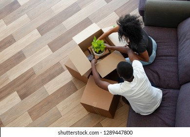 Black couple unpacking cardboard boxes in living room moving in out new home, african tenants renters packing stuff preparing for relocation house renovation, removals concept, top view from above
