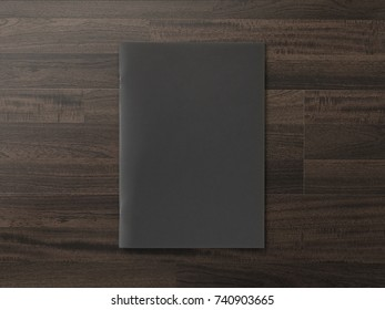 Black cover Magazine or Brochure on brown wooden background. Top view. Template concept for your showcase.