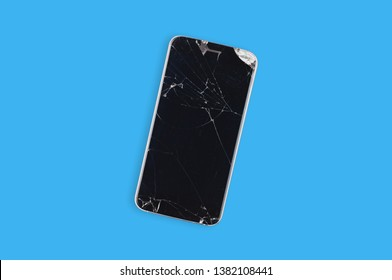 Black crashed smartphone with broken screen and body on blue table in service. Top view. Repair concept