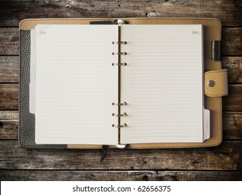 Black and cream leather cover of binder notebook on wood