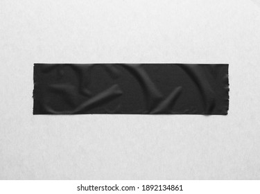 Black creased piece of matte cloth adheisive gaffer tape on grey cardboard background. Copy space for text.