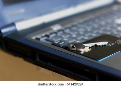 Black credit card and house key on a laptop keyboard.
