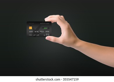 Black credit card in woman hand on dark background