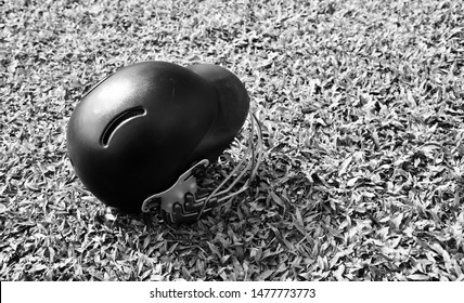 A black cricket helmet kept on a sports ground unique photo