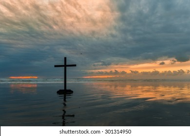Black cross on a beach with a cloudy sunset in the background.