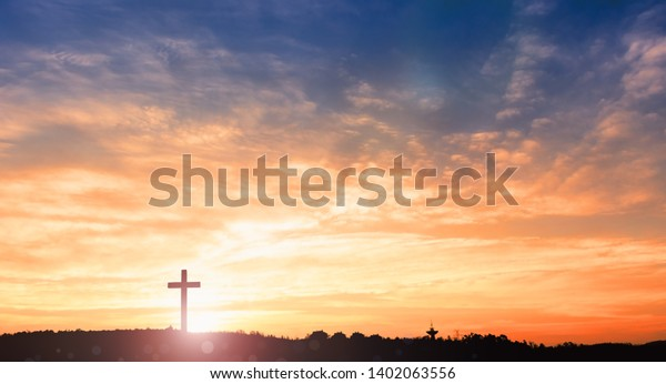 black cross religion symbol silhouette in grass over sunset or sunrise sky