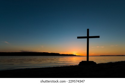 Black cross at sunset by a river shoreline.