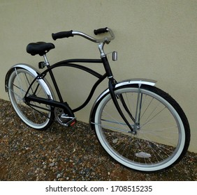 Black cruiser bicycle with wide chrome fenders and white walled tires against neutral colored wall.