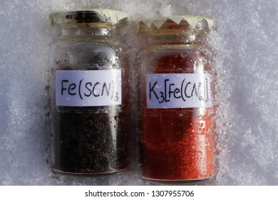 Black crystals of iron thiocyanate and orange crystals of potassium hexacyanoferrate in glass jars on the snow. Substances used in electroplating for the preparation of electrolytes.