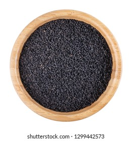 Black cumin, black caraway, nigella sativa or kalonji seeds in wooden bowl isolated on white. Top view.