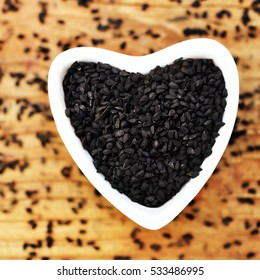 Black cumin (nigella sativa or kalonji) seeds in heart-shaped bowl on wooden background, selective focus