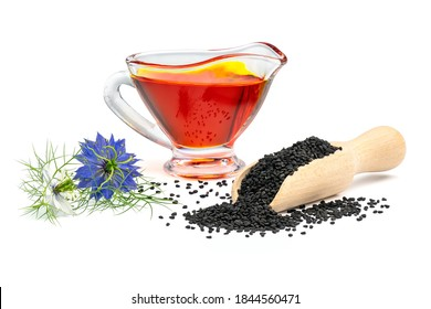 Black cumin oil in gravy boat and nigella flowers. Nigella sativa seeds in wooden scoop isolated on white background.