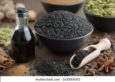 Black cumin or roman coriander seeds and black caraway oil bottles, aromatic spices on table: cardamom, anise, cloves, cinnamon,  turmeric. Ingredients for cooking. Ayurveda treatments.