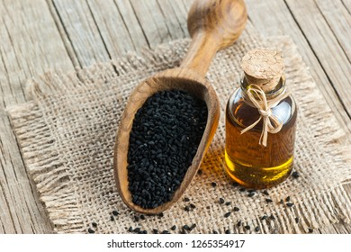 Black cumin seeds essential oil with wooden spoon or shovel on wooden background, Nigella Sativa in glass bottle. Organic herbal medicine for many diseases