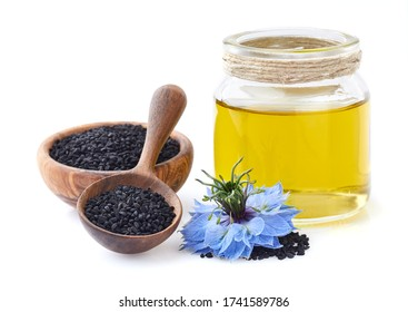 Black cumin seeds with oil and flower on white background