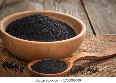 Black cumin seeds and a wooden spoon on a wooden table. Healthy, vegetarian, organic food concept.