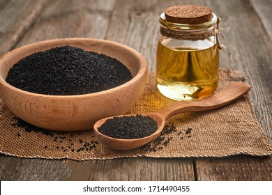 Black cumin seeds and a wooden spoon, bowl with bottle of oil on a wooden table. Healthy, vegetarian, organic food concept.