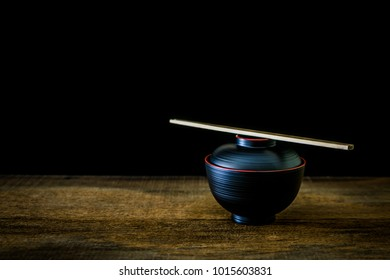 Black cup with chopsticks Japanese style on wooden floor with black background.