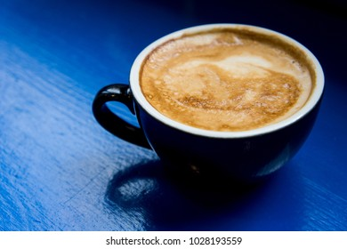Black cup of coffee with will on a wooden blue background