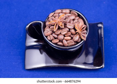Black cup filled with coffee beans and anise on blue color background