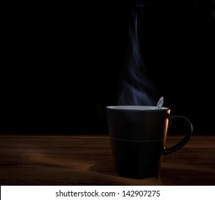 black cup of hot coffee on wood texture with dark background use for multipurpose
