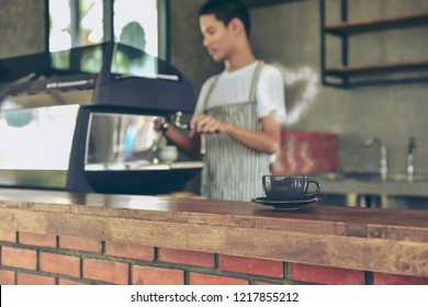 Black cup hot coffee with Smoke in Heart shape against Blurred of Young owner standing at the counter. Asian young barista and coffee machine in coffee shop counter  making drinks in cafe concept.