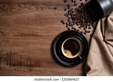 A black cup of hot espresso coffee with roasted coffee beans on old wooden kitchen table.Top view with space for your text.