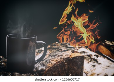 Black cup of hot steaming coffee sitting on an old log by campfire