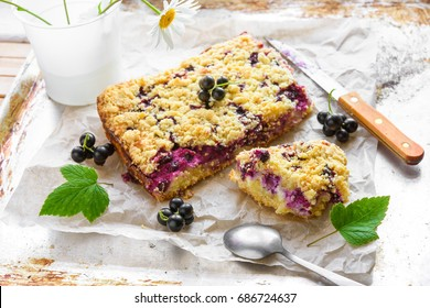 Black currant and cottage crumble cake with green leaves on baking paper and rustic background