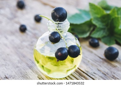 Black currant extract in a glass bottle. Medicinal tincture with black currant. Close-up.