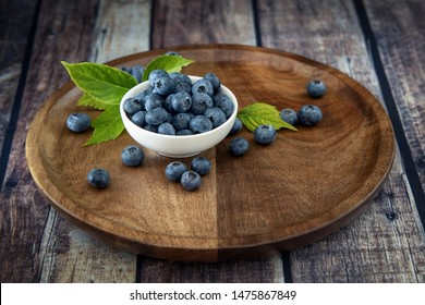 Black currant fresh ripe currant berries on a old vintage wooden table with green leaves. Juicy natural fruits currant.