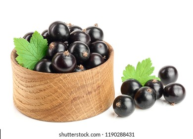 black currant with leaf in wooden bowl isolated on white background
