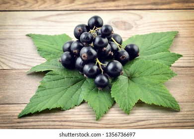 Black currant on wooden background. Black fresh berries.