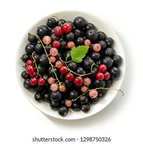 Black currant, red currant and pink currant with a leaf in a bowl on a white background. Isolated