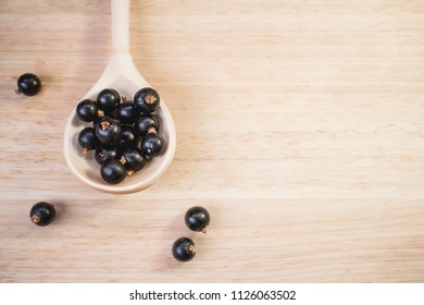 The black currant in a wooden spoon on a wooden table. Top view.