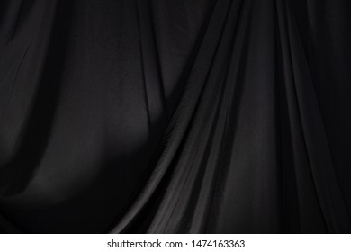 Black Curtain drape wave with studio lighting, Wallpaper Background Texture Detail